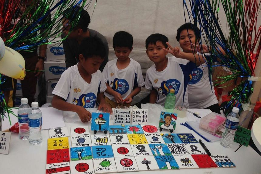 """Young """"entrepreneurs"""" selling painted tiles which they made themselves at the Kids' Bazaar at the Marina Bay Promontory on Sept 13, 2015."""
