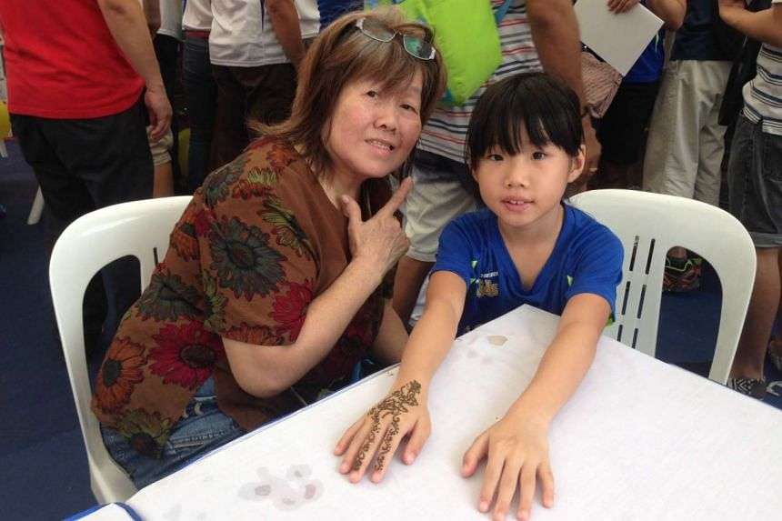"""Retiree Yap Yoke Lang, 68, and her granddaughter Sandra Lee, 7, at the Kids' Bazaar at the Marina Bay Promontory on Sept 13, 2015. Sandra got her hand decorated with henna. Said Madam Yap: """"Activities like that are better for children's health. Inste"""