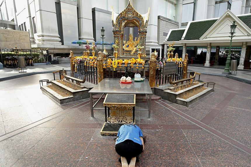 A woman worships to a statue of Lord Brahma, the Hindu God of Creation, at the Erawan Shrine in Bangkok, Thailand, on Sept 9, 2015.