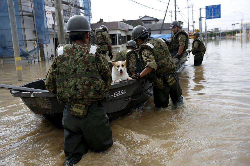 A pet dog being rescued by soldiers by boat at a residential area flooded by the Kinugawa river in Joso, Japan's Ibaraki prefecture.