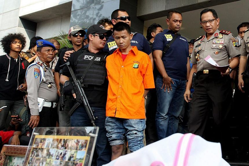 Indonesian police officers guard Mursalim (center), suspected of murdering a Japanese woman in her apartment, during a press conference at the Jakarta police headquarters, in Jakarta, Indonesia, on Sept 11, 2015.