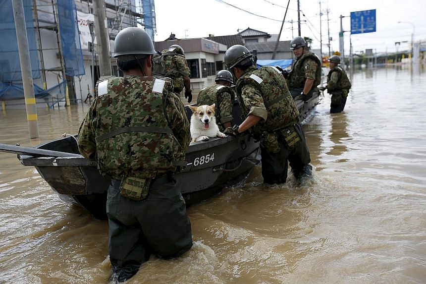 A pet dog being ferried to safety in Joso yesterday. Some 4,500 people were forced to stay in more than 20 facilities, such as schools, public halls and gymnasiums, as the region suffered a halt to water and power supply for the third night.