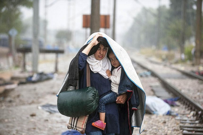 Migrants crossing the border between Greece and Macedonia last Thursday. Europe is divided over its refugee crisis.