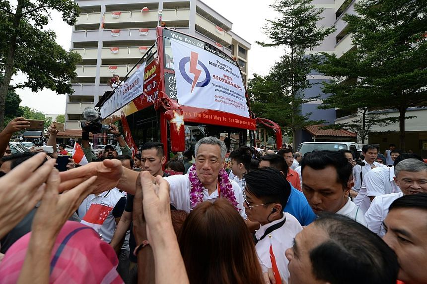 PM Lee and his Ang Mo Kio GRC teammates thanking their supporters yesterday.