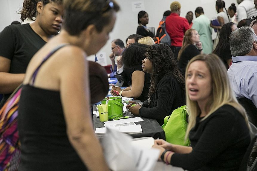Representatives at a job fair in Dallas, Texas, speaking with job-seekers earlier this month. The US Labour Department said last Friday that unemployment fell to 5.1 per cent last month, the lowest rate in over seven years.