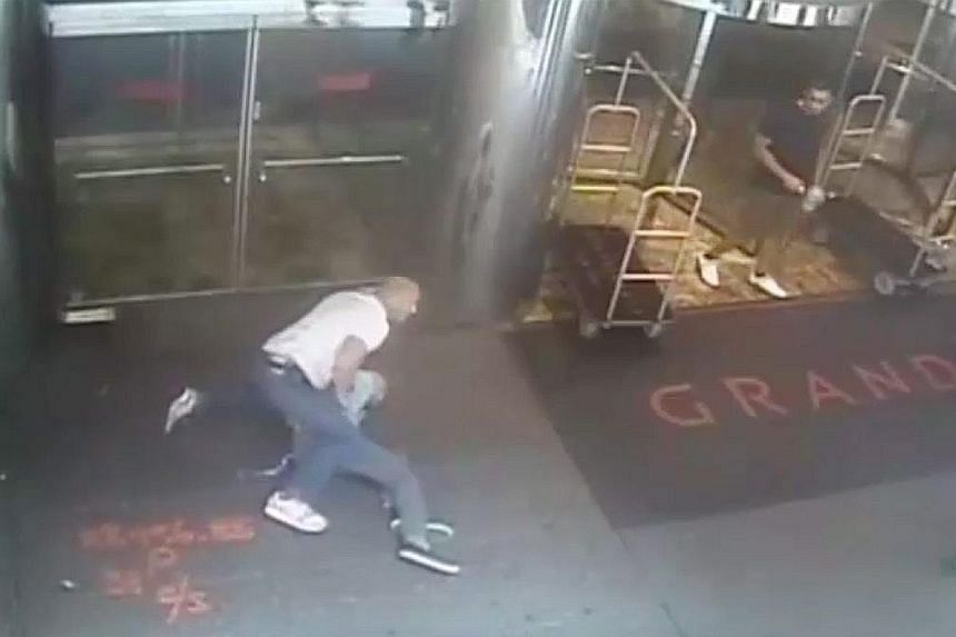 Retired professional tennis player James Blake (above) was mistaken for a suspect in a fraud case. In the video (left), officer James Frascatore (in white shirt) is seen wrapping an arm around Mr Blake's neck and throwing him onto the sidewalk.
