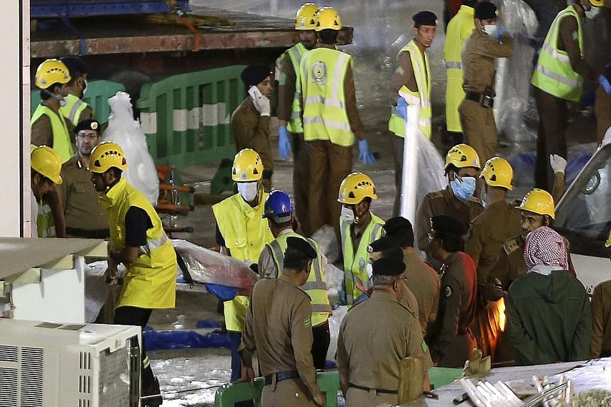 Emergency workers in Saudi Arabia removing a body from the site of the crane accident. The governor of the Mecca region, Prince Khaled Al-Faisal, has ordered an investigation into the incident. REUTERS The construction crane collapsed onto Mecca's Gr