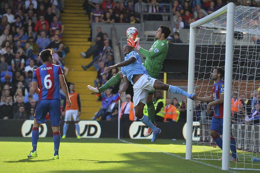 Manchester City's Vincent Kompany (centre left) challenges Crystal Palace goalkeeper Alex McCarthy.