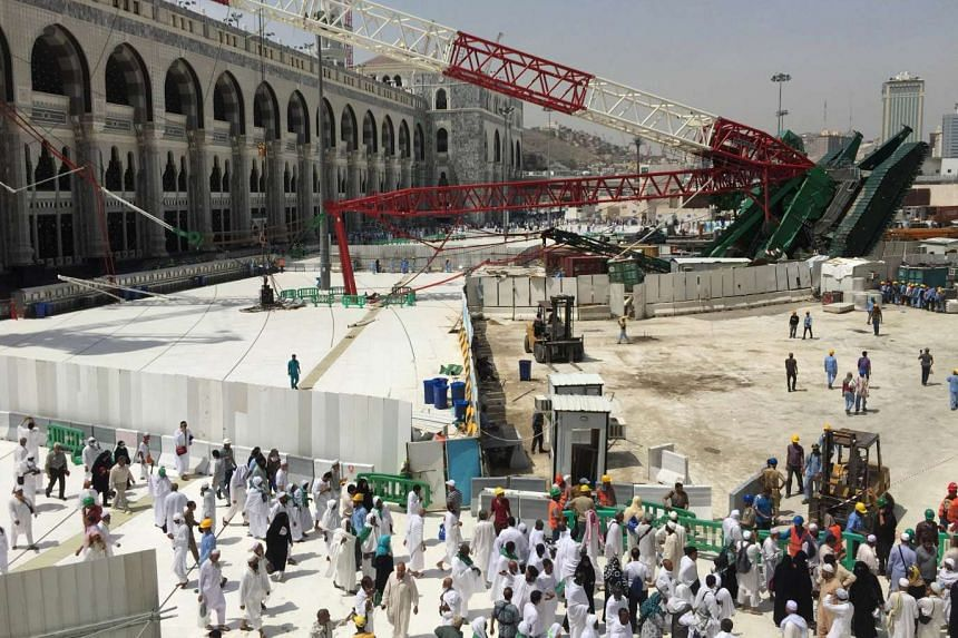 Muslim pilgrims walk near a construction crane which crashed in the Grand Mosque in the Muslim holy city of Mecca.