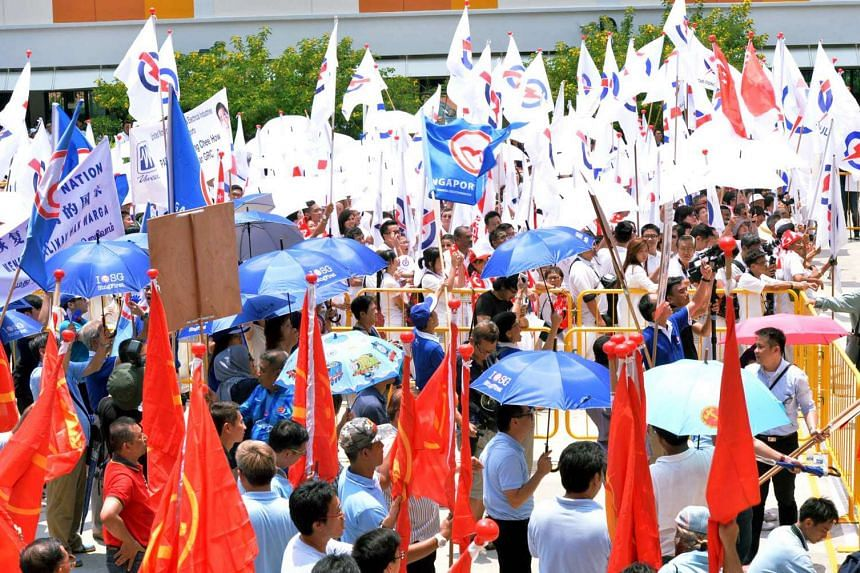 Supporters from the People's Action Party (PAP) (in white) and the Workers Party (WP) (in blue) waiting for the announcement of candidates for Jalan Besar GRC, Tanjong Pagar GRC, and Radin Mas SMC during Nomination Day.