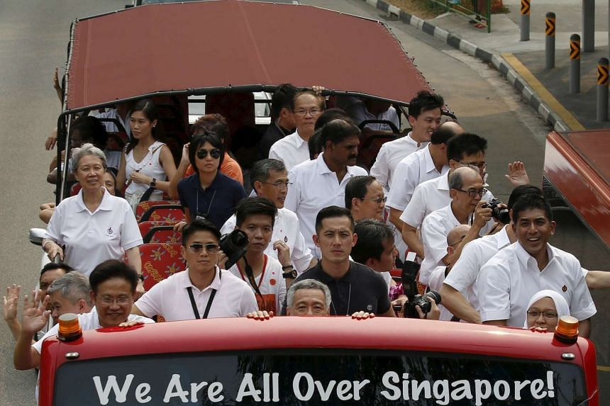 Singapore's Prime Minister and Secretary-General of the People's Action Party (PAP) Lee Hsien Loong (centre) ducks as his bus travels under a bridge while on route to thank supporters after the general election on Sept 12, 2015.