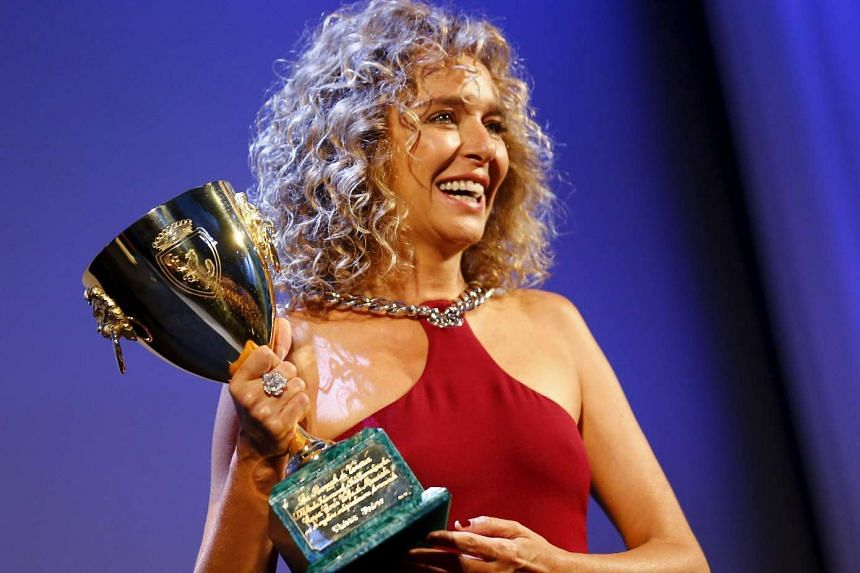 Actress Valeria Golino holds the Coppa Volpi for Best Actress.
