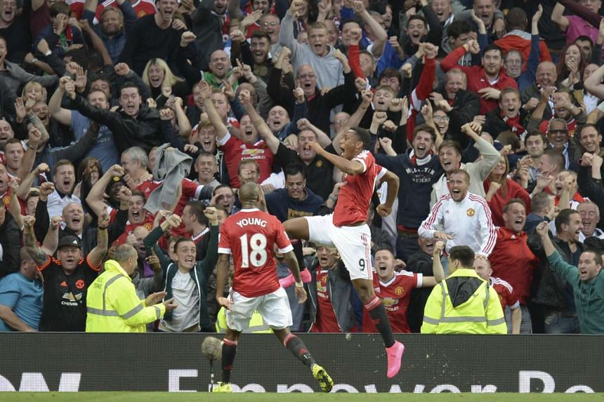 Manchester United's French striker Anthony Martial (right) celebrates scoring their third goal.