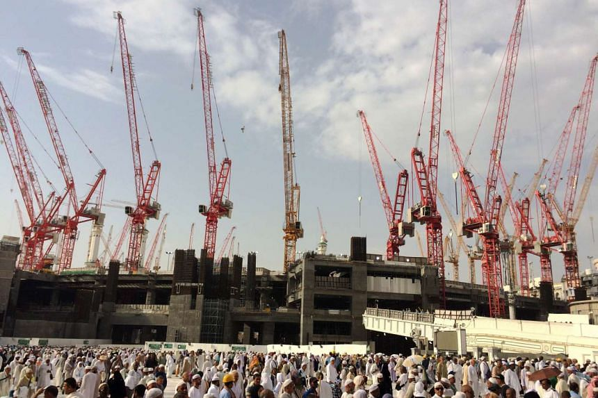 Muslim pilgrims walk in front of construction cranes as they arrived in Saudi Arabia's holy Muslim city of Mecca to perform the annual Muslim Hajj pilgrimage on Sept 12, 2015, a day after a crane collapsed at the Grand Mosque.