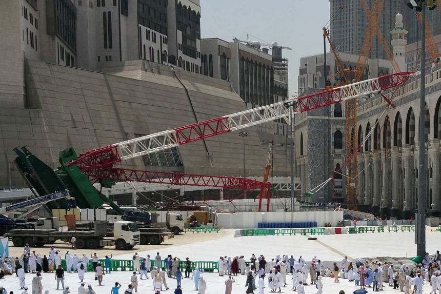Muslim pilgrims walk past the crane that collapsed the day before at the Grand Mosque in Saudi Arabia's holy Muslim city of Mecca on Sept 12, 2015.