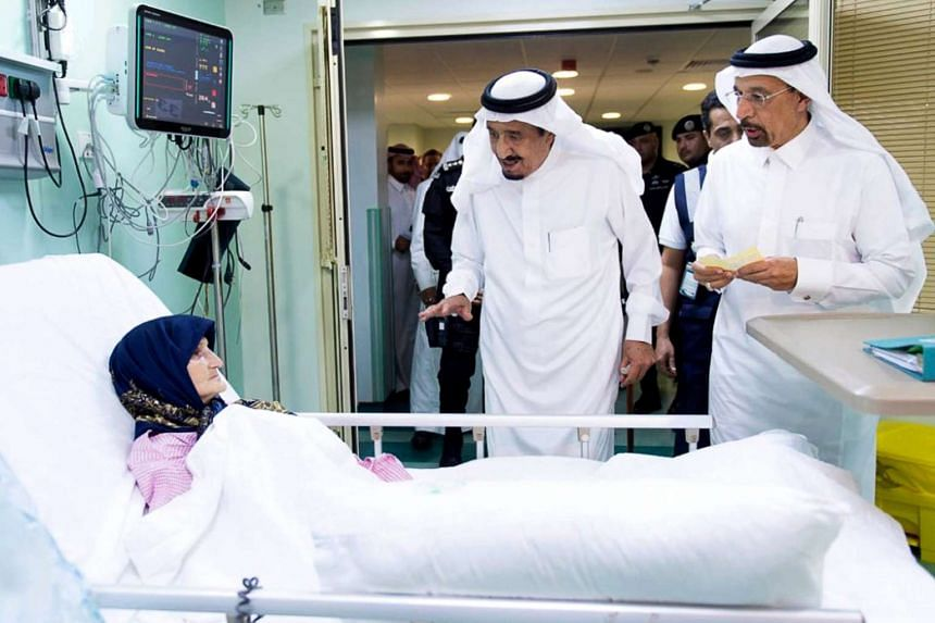 A handout picture provided by the Saudi Press Agency on Sept 12, 2015, shows Saudi King Salman bin Abdulaziz (centre) visiting a wounded woman at a hospital in Saudi Arabia's holy Muslim city of Mecca.