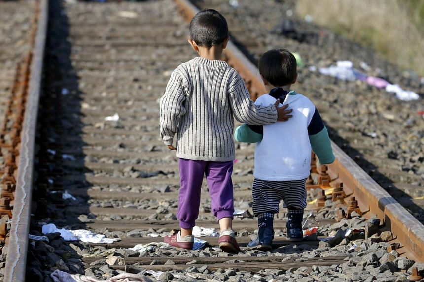 Migrant children stand on railways close to a migrant collection point in Roszke, Hungary on Sept 12, 2015.