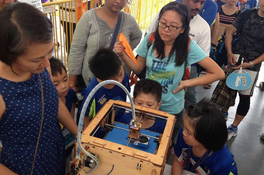 Children watching a 3D printer work at the Robotronics station at the POSB PAssion Run carnival on Sept 13, 2015. The Robotronics programme is organised by Tanglin-Cairnhill Community Club.