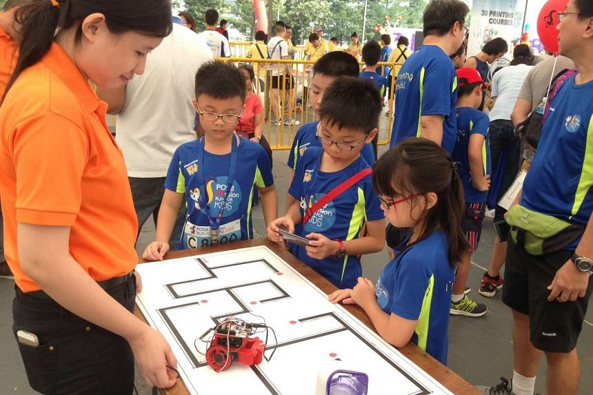 Children navigating a robotic toy car at the Robotronics station at the POSB PAssion Run carnival on Sept 13, 2015.