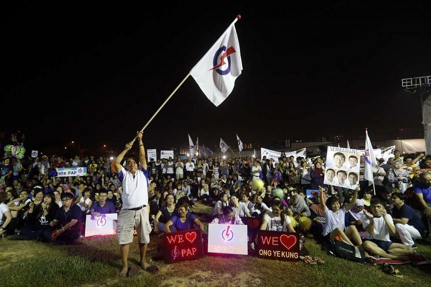 A PAP supporter waving the ruling party's flag at a rally on Sept 8 in Woodlands Drive 16 by the PAP's Sembawang GRC team, led by National Development Minister Khaw Boon Wan. The PAP won the GRC with 72.28 per cent of the votes against a National Sol