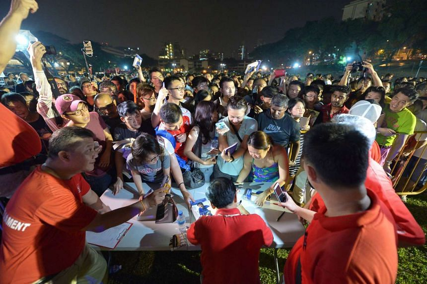Singapore Democratic Party chief Chee Soon Juan autographing books at a field in Commonwealth Avenue on Sept 6 after a rally. Dr Chee made his re-entry into politics this election, after having had to sit out the past two general elections as he was
