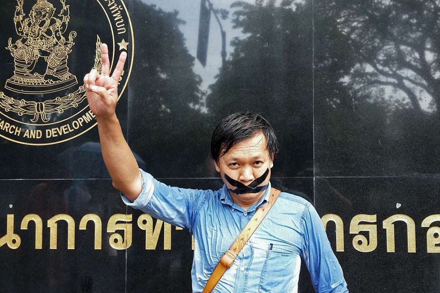 """Thai journalist Pravit Rojanaphruk flashes a V-sign as he stands with his mouth taped outside a military base in Bangkok where he had been summoned by the junta. A prominent Thai journalist has been detained by the junta for so-called """"attitude adjus"""