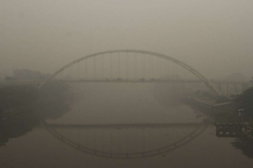 Vehicles drive on a bridge over the Siak river in the haze covered city of Pekanbaru, Riau Province on the Indonesian island of Sumatra, on Sept 14. 2015.