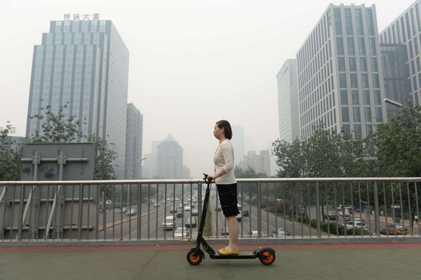 This picture taken on Jun 23, 2015 shows a woman riding an electric bike in smog covered Beijing.