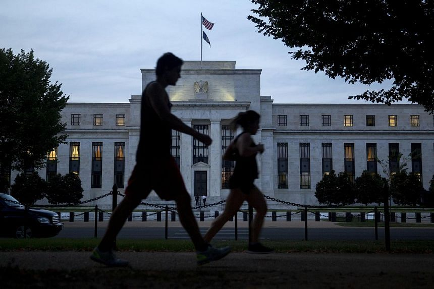 Pedestrians walking past the Marriner S. Eccles Federal Reserve building in Washington, DC.