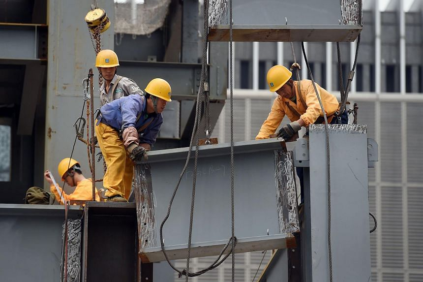Workers install a section of a steel beam on a construction site in Beijing on Sept 9, 2015.