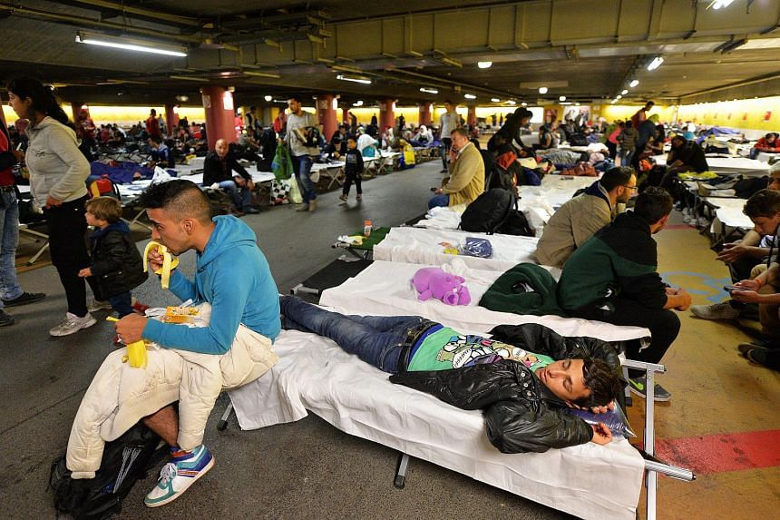 Refugees who earlier arrived on busses from the Hungarian border are temporarily accommodated on a parking deck in the railway station in Salzburg, Austria on Sept 13, 2015.