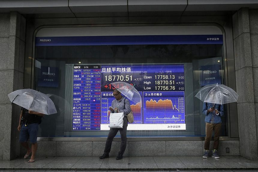 Pedestrians in front of an electronic stock board displaying the closing figure of the Nikkei 225 Stock Average outside a securities firm in Tokyo on Sept 9, 2015.