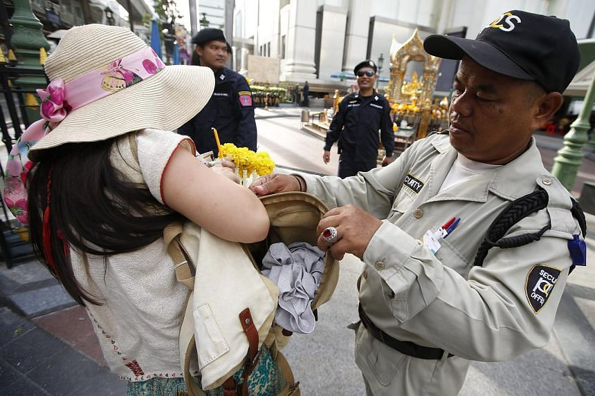 A security guard checks a worshipper's bag at the Erawan Shrine in Bangkok on Sept 9, 2015. An explosion ripped through the Hindu shrine on Aug 17, killing 20 people and wounding more than 100.
