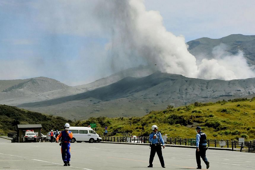 Smoke spews from the eruptive crater of Mount Aso as police officers and firefighters conduct an evacuation operation in Aso, Kumamoto prefecture, southwestern Japan, in this photograph taken by Kyodo on Sept 14, 2015.