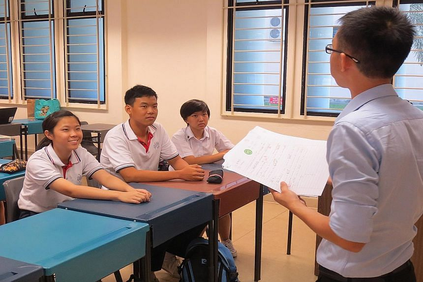 Dunman High students (from left) Law Xiao Xuan, Daniel Lee and Quek Zi Ning, all 17, are among the first in Singapore to take translation as an A-level subject. Their teacher Liu Zhiqiang snaps photos of any translation errors he spots in public area