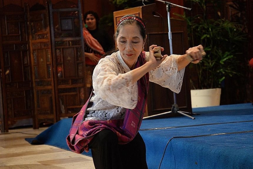 Left: Ms Ligaya Amilbangsa, 72, performing the pangalay, an ancient dance she has devoted her life to saving. She describes it as a cry for stillness in a world of violent shoving. Below: A dancer showing the audience the finer points of the slow dan