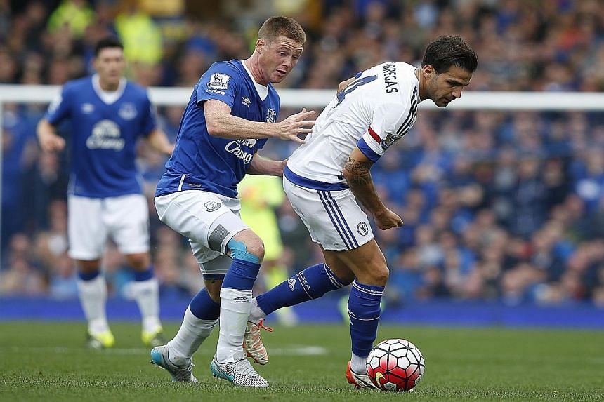 Cesc Fabregas (right), harried by Everton's James McCarthy, was as ineffectual as other team-mates in the 1-3 loss to Everton on Saturday.