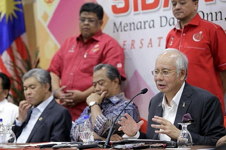 Malaysian Prime Minister Najib Razak speaking at the Umno Supreme Council meeting in Kuala Lumpur last week. With him are (from far left) Deputy Prime Minister Ahmad Zahid Hamidi and Umno deputy president Muhyiddin Yassin. Demonstrators at the Bersih
