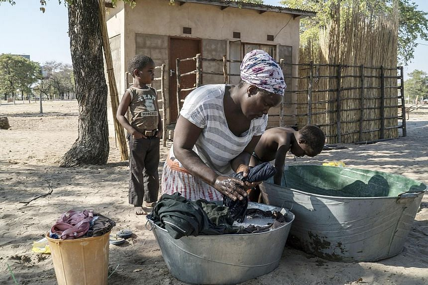 Ms Othusitse Ndozi doing laundry outside her home in Sanyuko, a remote village close to the Moremi Game Reserve in Botswana. Her husband once earned about US$100 (S$141) a month as a tracker and driver before trophy hunting was banned.