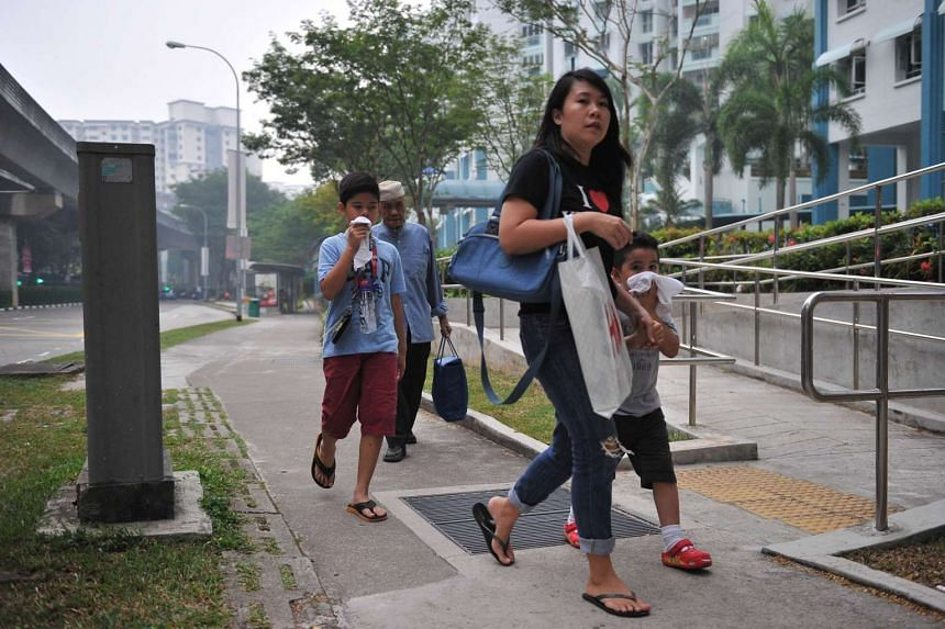 Children covering their faces with towels to deal with the haze at Rivervale Drive around 6.15pm on Sept 14, 2015.
