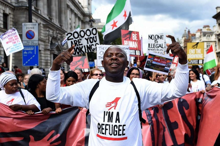 Demonstrators expressing solidarity with refugees march down Whitehall toward Parliament Square in London on Sept 12, 2015