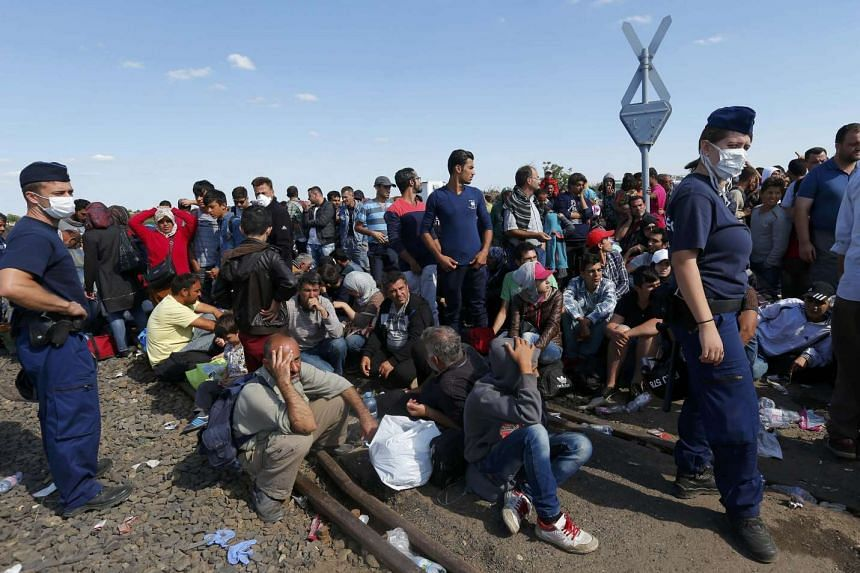 Hungarian policemen watch migrants near a collection point in Roszke village, Hungary Sept 9, 2015.