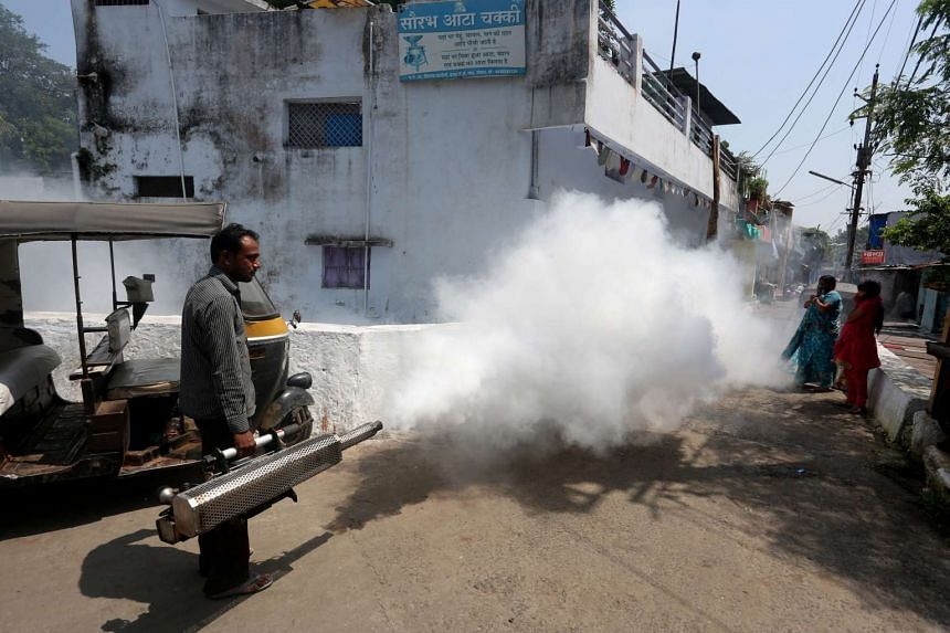 Municipal Corporation sanitation workers fumigate an area as part of an anti-malaria fumigation drive to curb breeding sites for mosquitoes causing dengue and malaria after the dengue outbreak in Bhopal, India, Sept 7,  2015.
