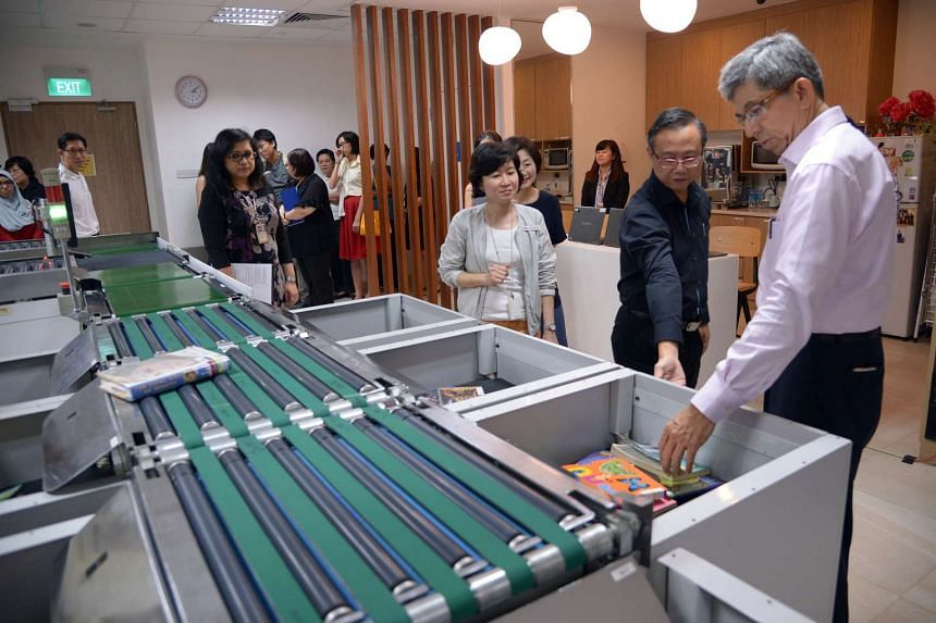 Minister for Communications and Information Yaacob Ibrahim (right) looks at the AutoSorter, which sorts out returned books at Sembawang Public Library, on Aug 28, 2015.