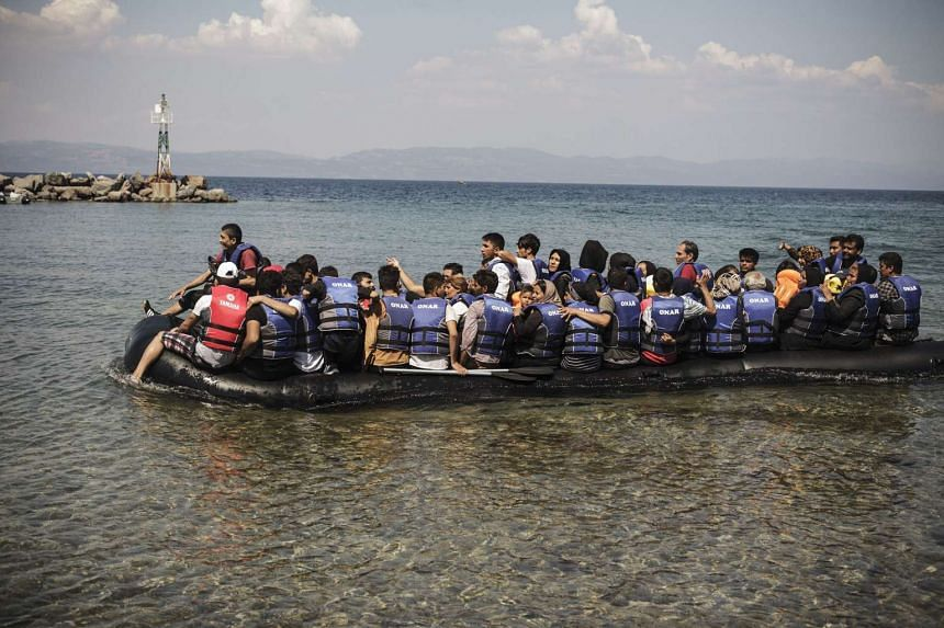 A dinghy carrying Iranian, Afghan, and Syrian migrants arrives on the Greek island of Lesbos on August 20.