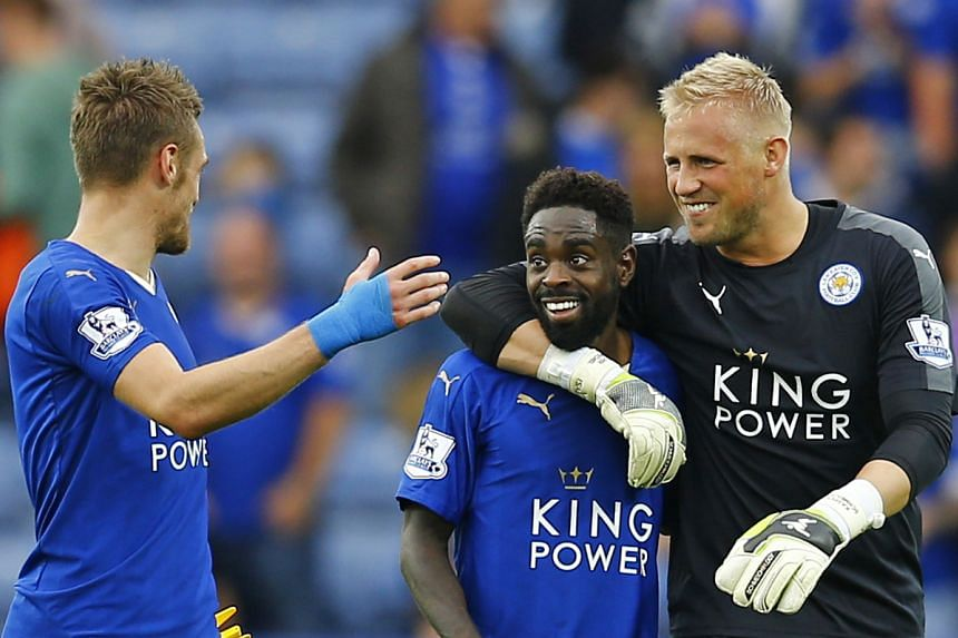 Leicester City's Nathan Dyer celebrates with Kasper Schmeichel and Jamie Vardy at full time.
