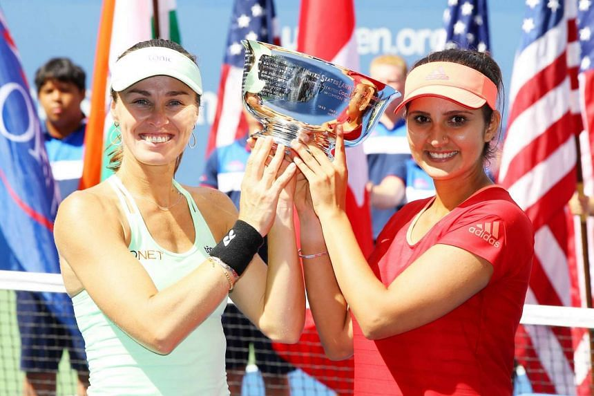 Martina Hingis (left) of Switzerland and Sania Mirza (right) of India celebrate with the winner's trophy fter their Women's Doubles Final at 2015 US Open on Sunday.