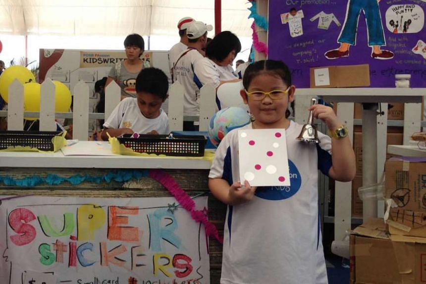Seven-year-old Seet Jiaxin at her booth, where she sold cards made from drawing paper and stickers.