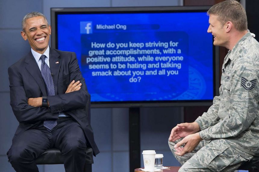 US President Barack Obama laughing at a question with moderator Tech Sergeant Nathan Parry (right) during a meeting with the US military at Fort Meade on the 14th anniversary of the 9/11 attacks.