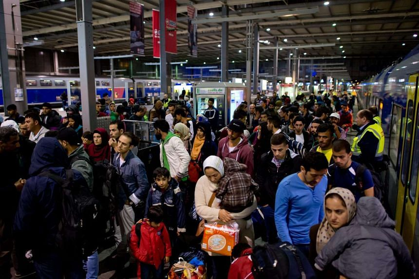 Recently arrived refugees at a train station in Germany's city of Munich yesterday. Some 13,015 refugees arrived in Munich last Saturday, and at least 1,400 were expected to reach the southern city yesterday, as Munich Mayor Dieter Reiter made a plea